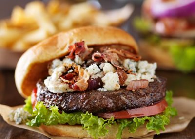 gourmet bacon and bleu cheese burgers with beer in background